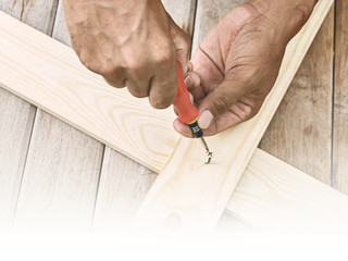 Man hand with screwdriver and screw or bolt on wooden plank