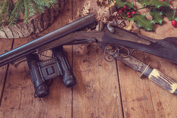 Beautiful hunting still life: old hunting gun, look-see, knife, dry leaves and berries on old wooden background with copy space