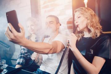 Smoke hookah shisha in bar and nightclub, team of friends take selfie photos on phone