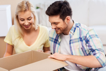 mortgage, moving and real estate concept - happy couple looking inside box or parcel at home