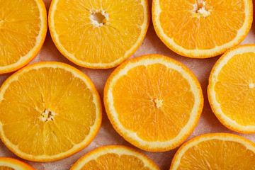 Abstract background with citrus orange slices on parchment paper. Close up. Top view. Studio photography.