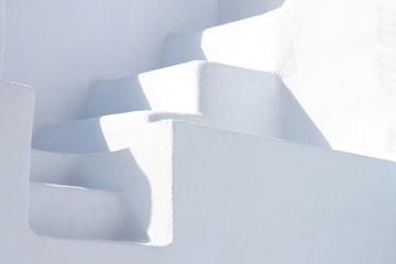 White stone staircase between two white walls, Oia, Santorini, Greece.