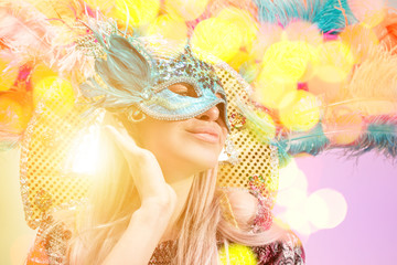 Beautiful young woman in carnival mask. Beauty model woman wearing masquerade mask at party over holiday background with magic glow. Christmas and New Year celebration. Glamour lady with perfect make