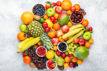 Circle made of healthy colorful fruits, strawberries raspberries oranges plums apples kiwis grapes blueberries mango persimmon on the white table, top view, copy space for text, selective focus