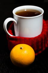 White mug with tea and warm knitted scarf on the dark background. Toned