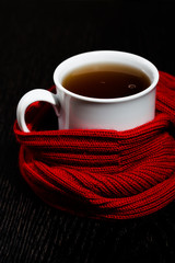 White mug with tea and warm knitted scarf on the dark background