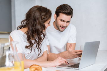 attractive woman looking at boyfriend using laptop in kitchen