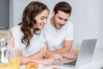 cheerful boyfriend and girlfriend smiling while using laptop in kitchen