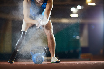 Young paralympic athlete applying talc on his hands while leaning over kettlebell at stadium