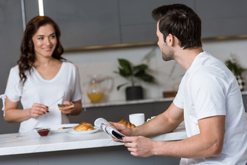 selective focus of man holding newspaper and looking at woman in kitchen