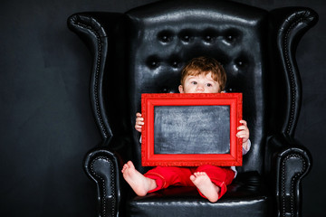 Little boy sitting on the armchair with red framed picture on the St. Valentine's day. little feet close-up
