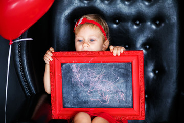 Little girl sitting on the armchair with red framed picture on the St. Valentine's day. little feet close-up