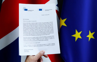 A copy of a joint letter from EU Commission President Juncker and EU Council President Tusk sent to British PM May is displayed with a British Union Jack and an EU flags in this picture illustration
