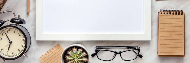 White mockup frame on a marble table. Panoramic view from above. Desk with alarm clock, cactus, glasses and other office accessories.