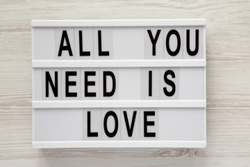 Modern board with text 'All you need is love' over white wooden background, top view. From above, flat lay, overhead.
