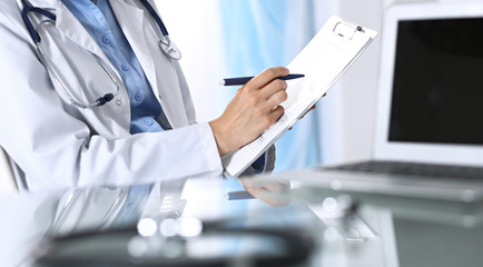 Female doctor filling up medical form on clipboard, closeup. Reflecting glass table is a physician working place. Healthcare, insurance and medicine concept