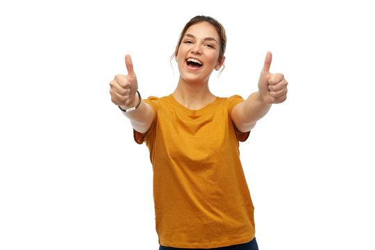 gesture and people concept - happy smiling young woman or teenage girl in orange t-shirt showing thumbs up over white background