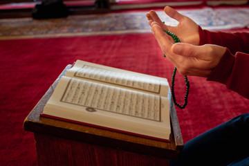 Muslim people hands prays and reading the Quran at the mosque