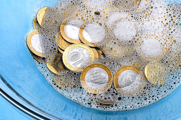 Money-laundering. Coin laundering in soapy water. The concept of tax evasion.