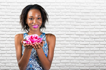 Beautiful young african woman holding rose blossom