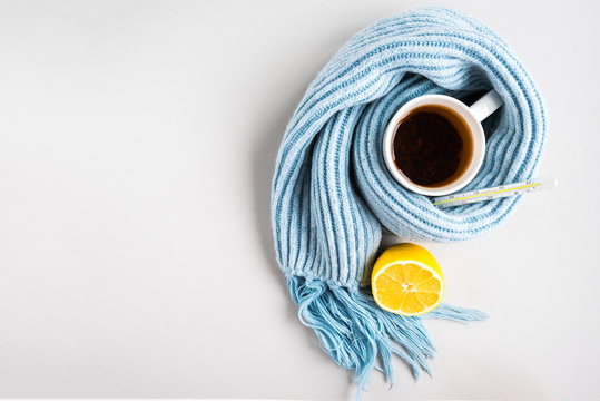 Tea cup with thermometer, blue scarf, pills and lemon on gray background. Flu season, disease.
