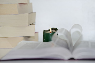 Heart shape from paper book against focused green candle and pile of books