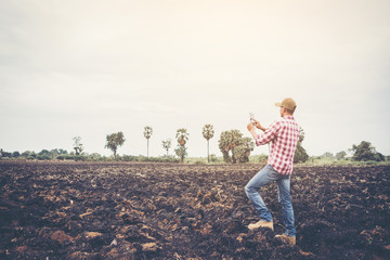 smart farmer using technology in an agriculture field ;man checking by using tablet in farm field