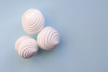 White marshmallows on blue background. Flat lay, copy space