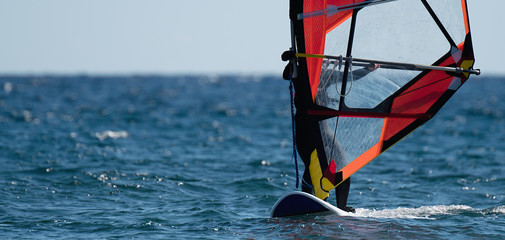 Windsurfer surfing the wind on waves in ocean, recreational sporting activity