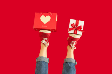 feet with a gift for the holidays on an isolated red background, a girl with a gift, giving gifts, discounts. Valentine's Day.
