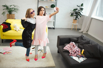 Stylish young teenagers stand in room and pose on phone camera. They wear clothes for adult women. Brunette hold camera. They take selfie.