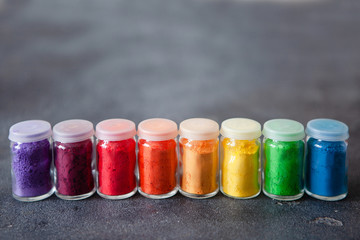 Bright colourful powdered pigments in glass bottles for Indian holi festival on dark slate background, copy space Fototapete