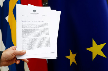 A copy of a letter from British PM May sent to EU Council President Tusk and EU Commission President Juncker is displayed with an EU flag in Brussels, in this picture illustration