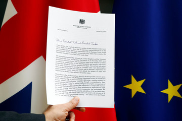 A copy of a letter from British PM May sent to EU Council President Tusk and EU Commission President Juncker is displayed with a British Union Jack and an EU flag in Brussels, in this picture illustration