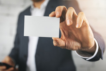 businessman hand showing blank white business card closeup