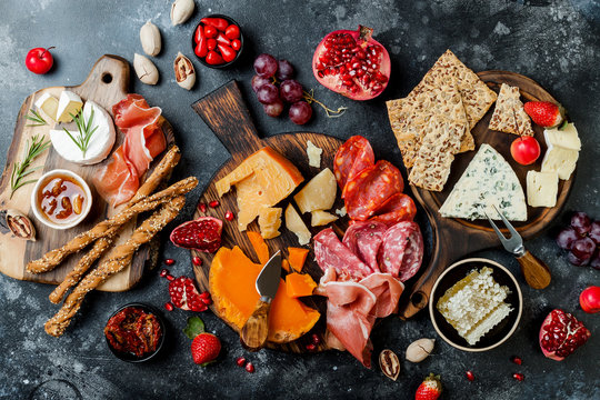 Appetizers table with italian antipasti snacks. Brushetta or authentic traditional spanish tapas set, cheese and meat variety board over black stone background. Top view, flat lay
