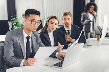 professional young multiethnic business people working with papers and laptop in office