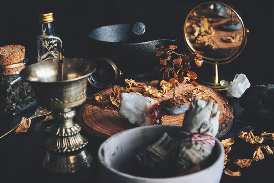 Wiccan witch altar working space. Looks busy and messy filled with dried herbs, citrine crystal, amber decoration, sage stick, gold colored incense burner, gold mirror, mortar and pestle in background