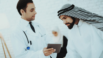 Male Doctor Consulting Arabic Man at Hospital