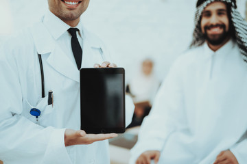 Male Doctor Holding Tablet Arabic Man at Hospital
