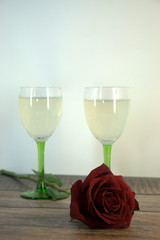 Two glasses of champagne and a red rose on a wooden table.