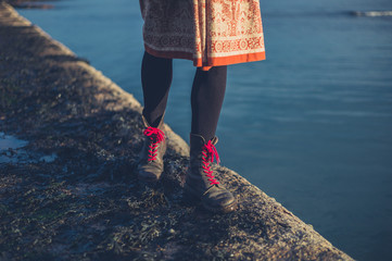 Woman in boots by the water