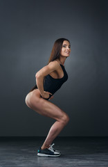 beautiful athletic young woman with muscles doing exercises  bodybuilding