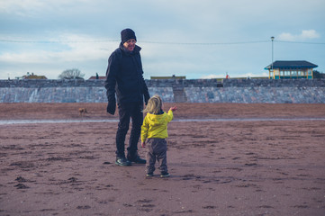 Toddler with grandfather on beach in winter