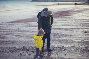 Toddler and grandmother on the beach in winter