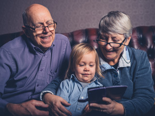 Grandparents and toddler looking at smartphone