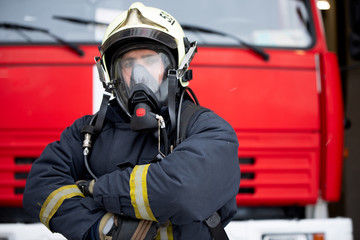 Picture of man fireman in gas mask near fire truck