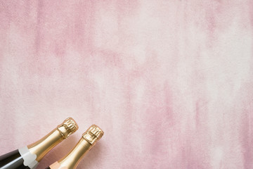 Champagne bottles on pink background. Copy space, top view
