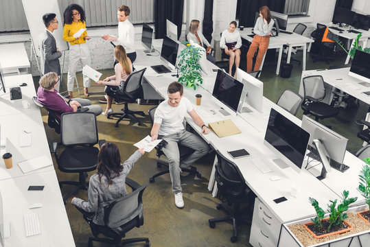 high angle view of professional young colleagues working with papers and computers in open space office