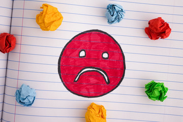 Sad face with colorful crumpled paper balls on notebook sheet
